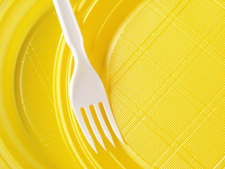 yellow disposable plates with fork                                photo