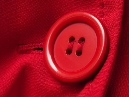 red button closeup with shallow DOF red clothes background                           photo