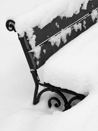 park bench fragment under the snow in black and white                             photo