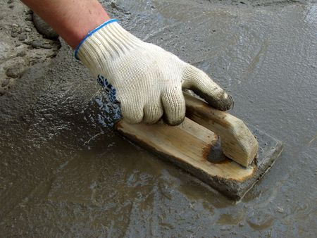 hand spreading cement with trowel                                photo