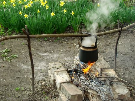 boiling water in old sooty kettle on the hiking campfire                                photo