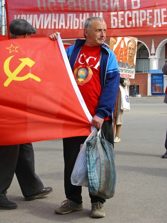 remonstrance:  Kaluga City, Russia - May 1,  2009 -  participant of traditional Communists meeting on The Day of the International Workers Solidarity (that called in USSR) with flag. Now, in Russia this holiday is called