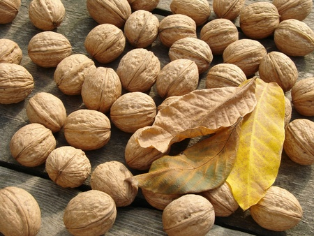 walnuts with leaves on old wooden background Stock Photo - 10704360