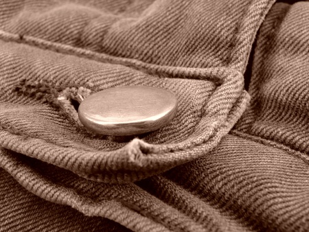 stitching: sepia toned denim fragment with a button