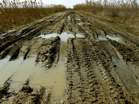 off road vehicle: dirty rural road with deep tire tracks