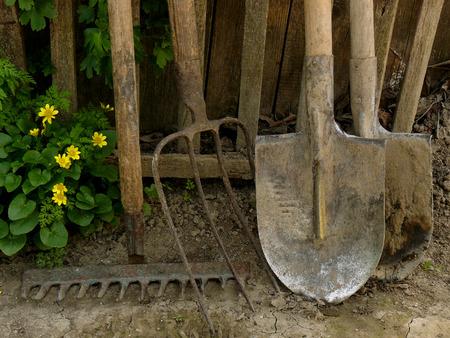 hayfork: some garden tools near old wooden fence Stock Photo