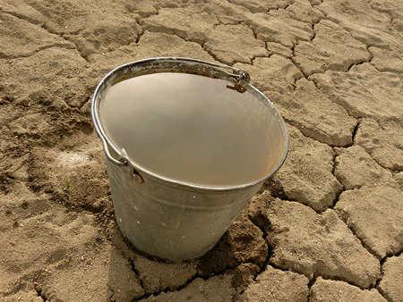 reclamation: bucket full of water on dry soil background