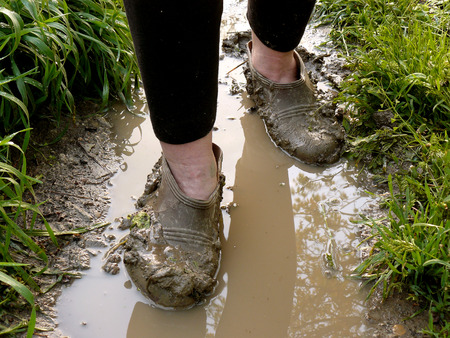 walking through the rain puddle in the muddy rubbers photo