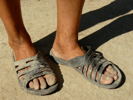 dirty feet: dirty male feet in rubber slippers on dried earth Stock Photo