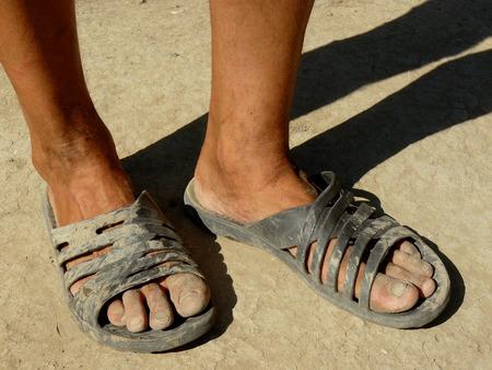 pies masculinos: pies masculinos sucios en zapatillas de goma en la tierra seca Foto de archivo