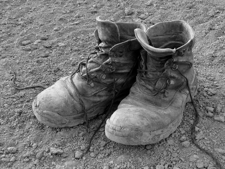 work boots: pair of well worn work boots in black and white