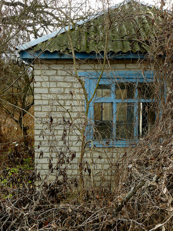 dilapidated wall: small abandoned house surrounded by leafless trees Stock Photo