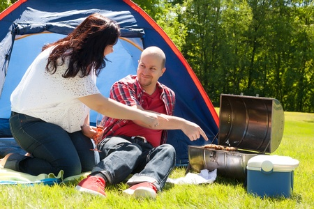 meat lover: Happy young couple is relaxing on a camping Stock Photo