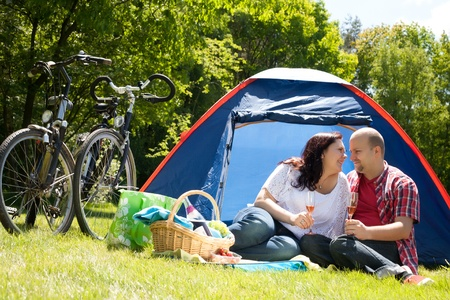 bivouac: Happy young couple is relaxing on a camping Stock Photo