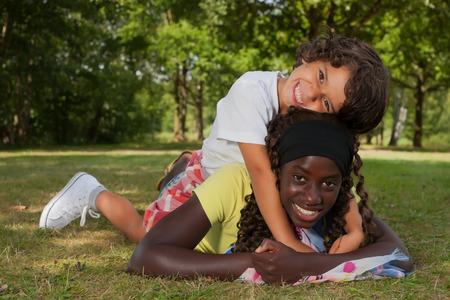 niños de diferentes razas: Niños africanos felices que tienen una buena dat en el parque LANG_EVOIMAGES