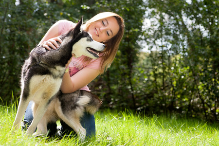 husky: Young woman and her husky in the forest