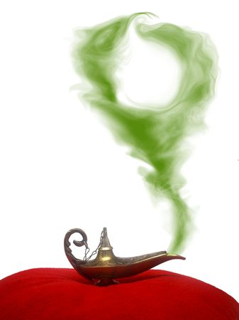 A magical genie lamp with smoke on a red velvet pillow with circular, green smoke. Stock Photo
