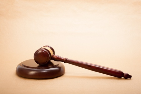 A wooden gavel and soundboard on a light brown background. Stock Photo
