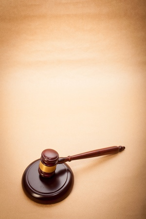 verdicts: A wooden gavel and soundboard on a light brown background. Stock Photo