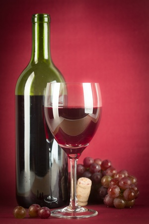 glass half full: A bottle of red wine, a glass half full and grapes on a vintage red background.