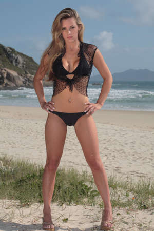 A blonde, 20-30 year old female model on the beach, in Florian�polis - Brazil. This is part of a series. Have a look at the other photos of this model in various outfits and poses.