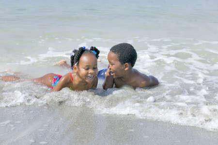 hermanos jugando: J�venes African American hermano y hermana de disfrutar de un d�a jugando en la playa