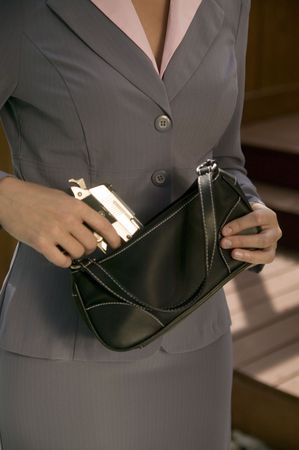 defense: A woman in a business suit takes a gun from her purse.