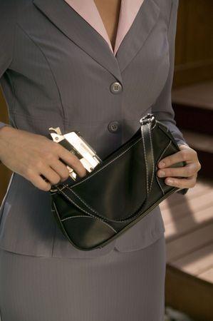 defensa personal: Una mujer en un traje de negocios toma un arma de su bolso.  Foto de archivo
