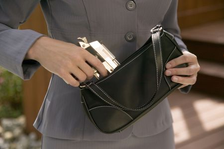 A woman in a business suit takes a gun from her purse. photo