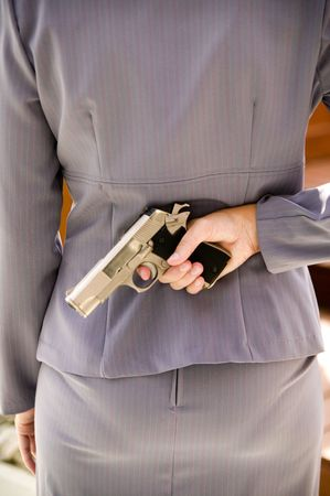 A woman in a business suit holds a gun behind her back photo
