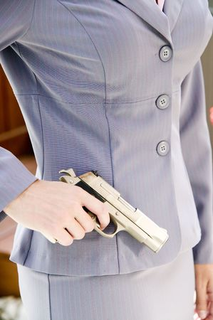 A woman in a business suit holds a gun by her side photo