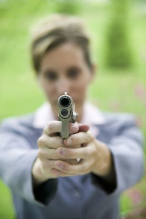 A woman in a business suit points a gun at the camera photo