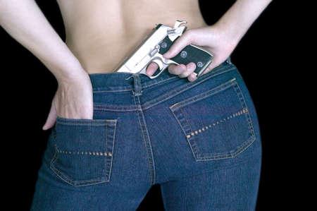defensa personal: Mujer escondiendo un arma de fuego en la parte de atr�s de sus jeans