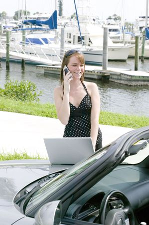Attractive young red head business woman stays in touch on the go with the latest technology in cell phones and laptops photo