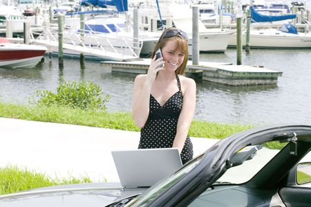 sucessful: Attractive young red head business woman stays in touch on the go with the latest technology in cell phones and laptops