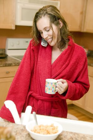 red bathrobe: A young woman with wet hair in a red bathrobe holding a cup of coffee whilst talking on the phone in her kitchen