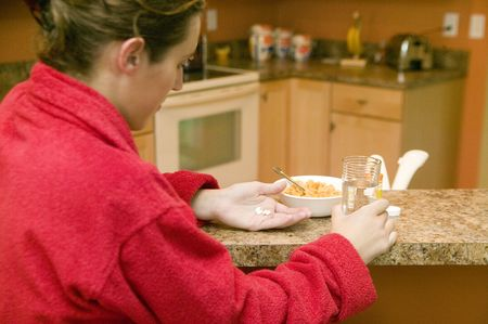 red bathrobe: A young woman in a red bath robe taking pills with her breakfast
