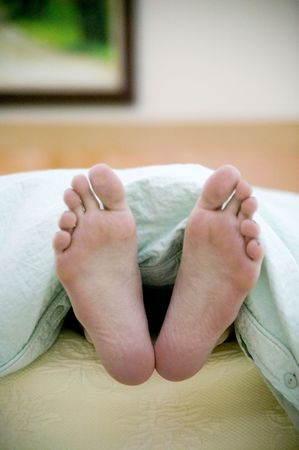 Portrait photograph of a pair of womans feet sticking out the end of the bed Stock Photo - 734726