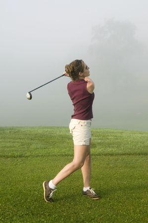 teen golf: Una joven mujer disfruta de una ronda de golf en una ma�ana de verano niebla