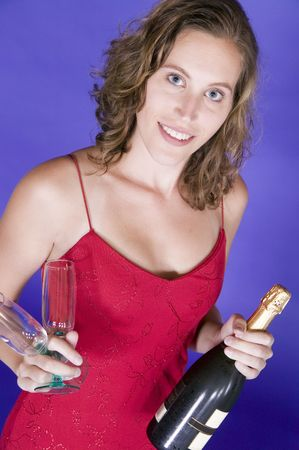 evening gown: Attractive young woman in evening gown with a pair of champagne glasses and a bottle of champagne.