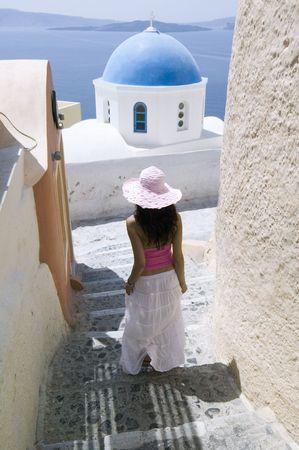 santorini greece: Beautiful young Greek woman on the streets of Oia, Santorini, Greece. Stock Photo