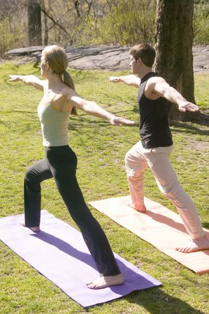 pratice: An attractive young man and woman pratice Yoga in central park