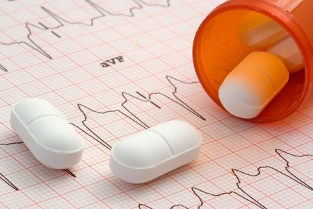 A close up of a EKG with a bottle of pills sitting on it. photo