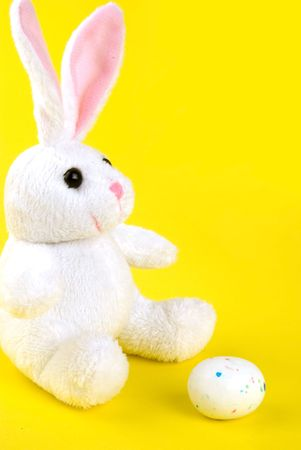 bunnie: the easter bunnie sitting in front of a white egg Stock Photo