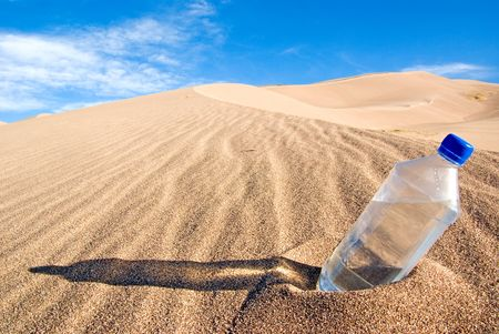 A cold bottle of water sitting in a sand dune photo