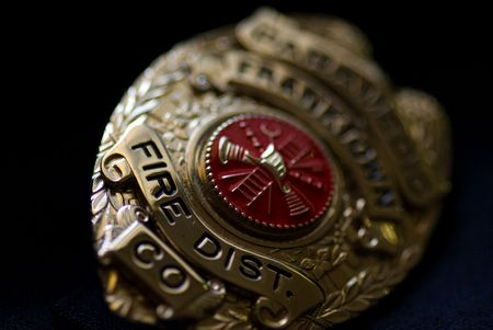 id badge: A badge from a fire fighter on a dark background