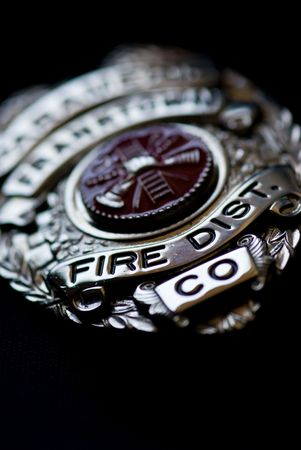 A badge from a fire fighter on a dark background photo