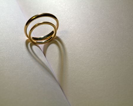 Two rings that cast a shadow heart on a book photo