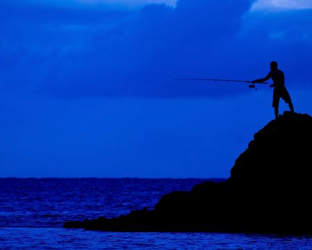 The dark figure of a man fishing from a rock into the sea photo