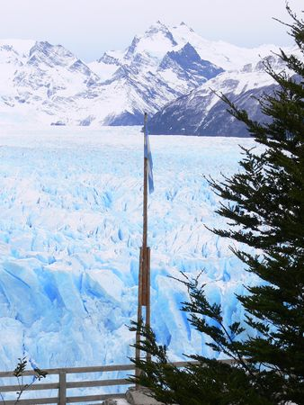 This photograph is of the Perito Moreno Glacier near El Calafate, Patagonia in Southern Argentina. This photograph has it all, snowcapped mountains, a world renouned glacier, a lake as well as some greenery. It also includes the flag of Argentina photo